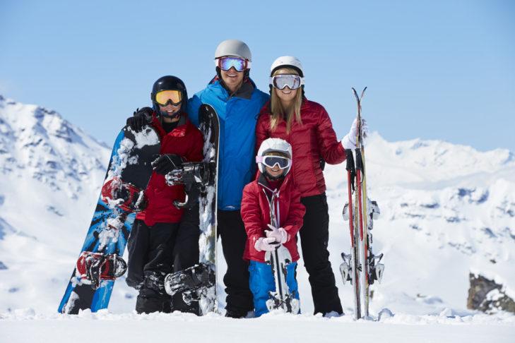 Skifahrer und Snowboarder genießen den Tag gemeinsam in den Bergen.