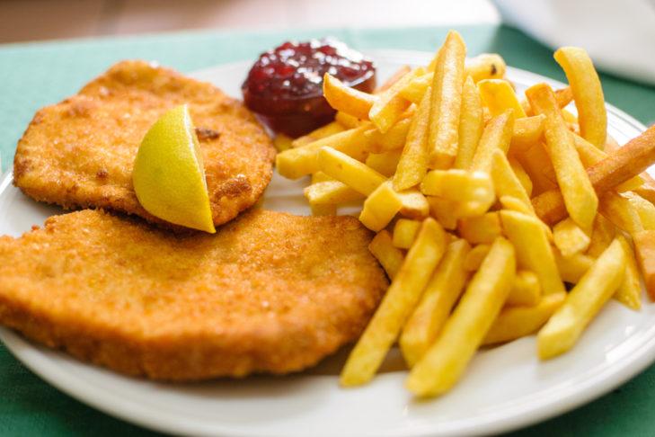 Kulinarischer Klassiker: mit Pommes Frites und Preiselbeeren - das Wiener Schnitzel.