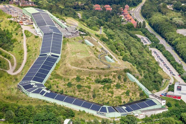 Luftbild der Skihalle in Bottrop. Ihr Gefälle entsteht, da sie günstig an einen Hang gebaut wurde.