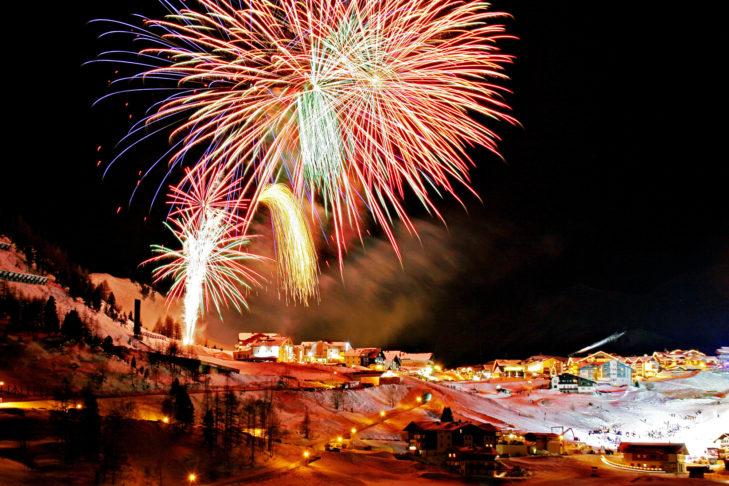 Feuerwerk über einer verschneiten Dorflandschaft.