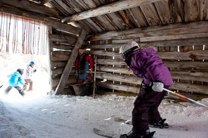 Kinder fahren durch das Hexenhaus im Skigebiet Silvapark Galtür.