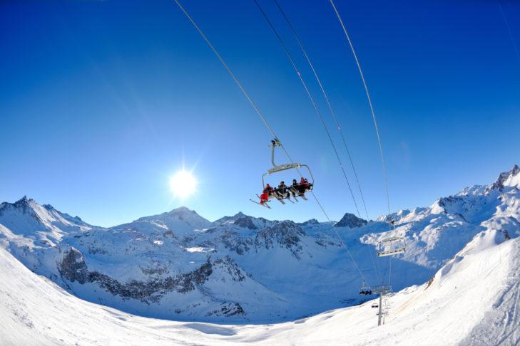Blick auf einen Sessellift vor verschneiten Berggipfeln.