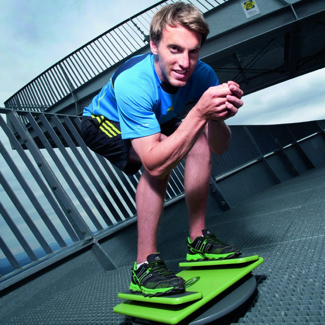 Ski-Profi Fritz Dopfer in der Abfahrtshocke: Spezielle Geräte wie das abgebildete Trainingsbrett simulieren die Kurvenlage auf der Skikante.