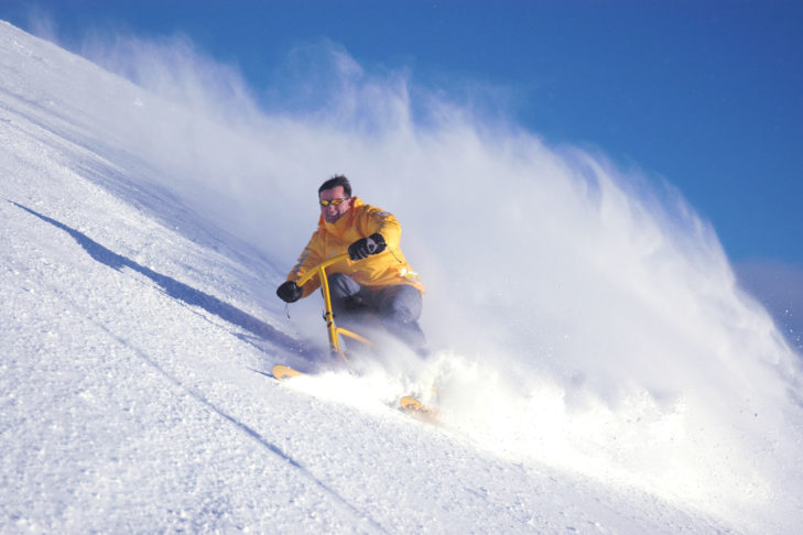 Auf dem Snowbike geht es auf drei Kurzskiern dem Berg runter.