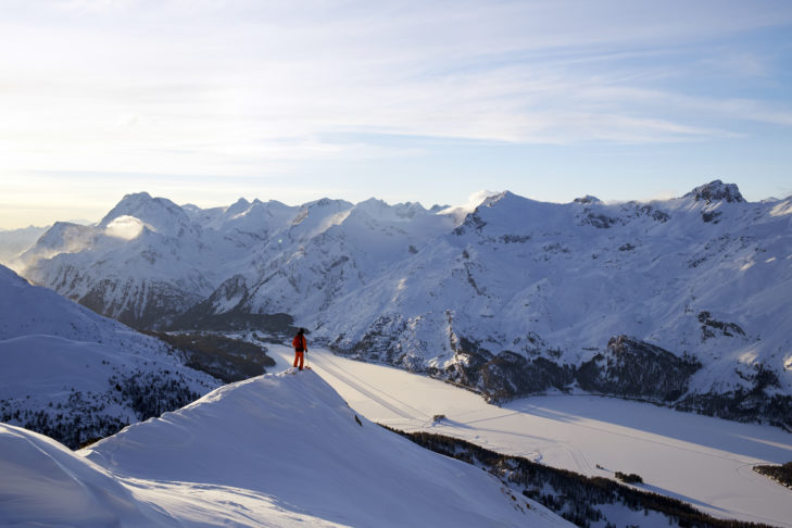 Freerider im Skigebiet Corvatsch/Furtschellas unterhalb des Piz Grialetsch. Im Hintergrund die Ortschaft Maloja und der gefrorene Silsersee.