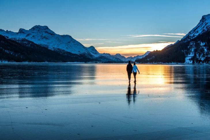 Winterwanderer im Sonnenuntergang auf dem gefrorenen Silvaplanersee.