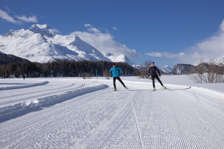 Längläufer auf einer Skating-Loipe im Talboden des winterlichen Engadin.