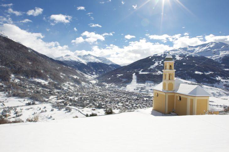 Luftaufnahme von Bormio mit der Kirche auf einer Anhöhe.