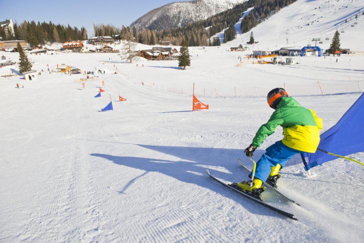 Junger Skifahrer beweist heiße Kanten im Kidspark.