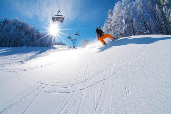 Snowboarder auf der Piste im Skigebiet Mariborsko Pohorje.