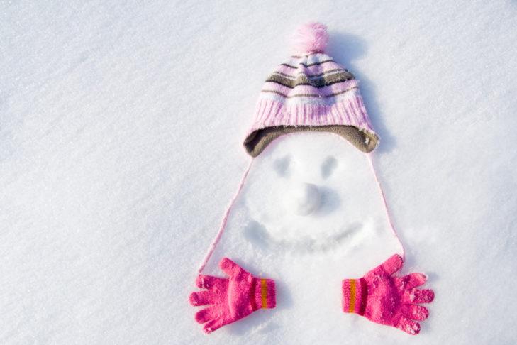 Mütze und Handschuhe mit Smiley im Schnee