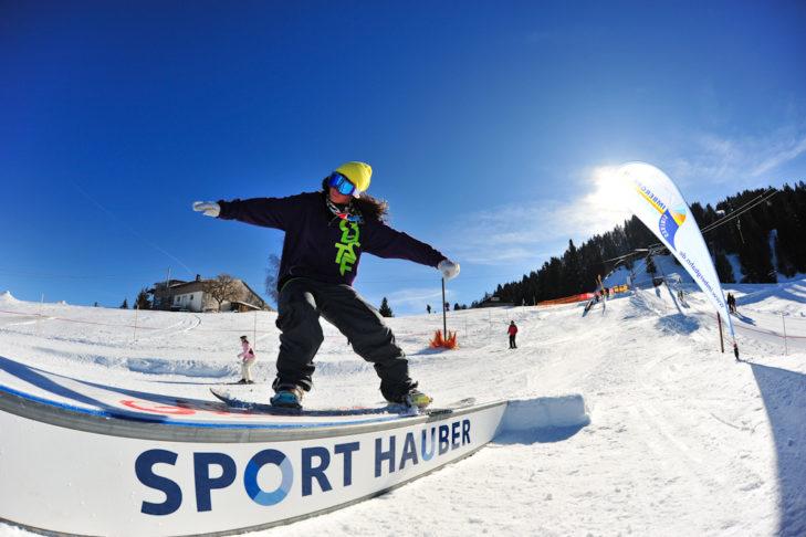 Snowboarder übt sich an einer Box im Steibis Snowpark Oberstaufen.