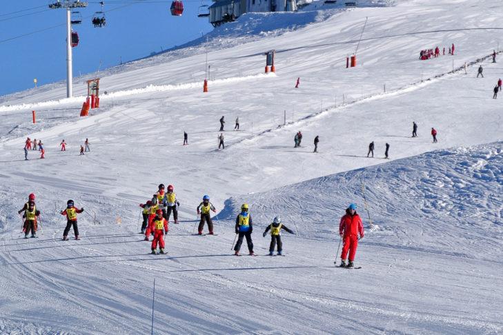 Eine Skischule unterwegs im Skigebiet Chamrousse.