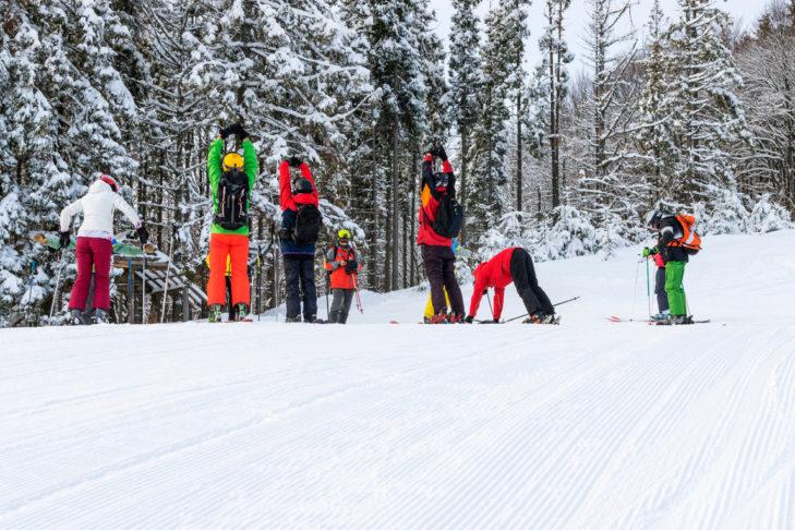 Aufwärmübungen zum Start eines Skitages helfen dabei, Verletzungen zu vermeiden.