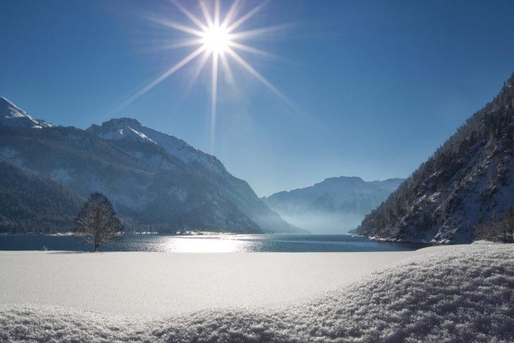 Ein besonders romantisches Panorama beim Winterwandern findet man am, in der Sonne glitzernden, Achensee.